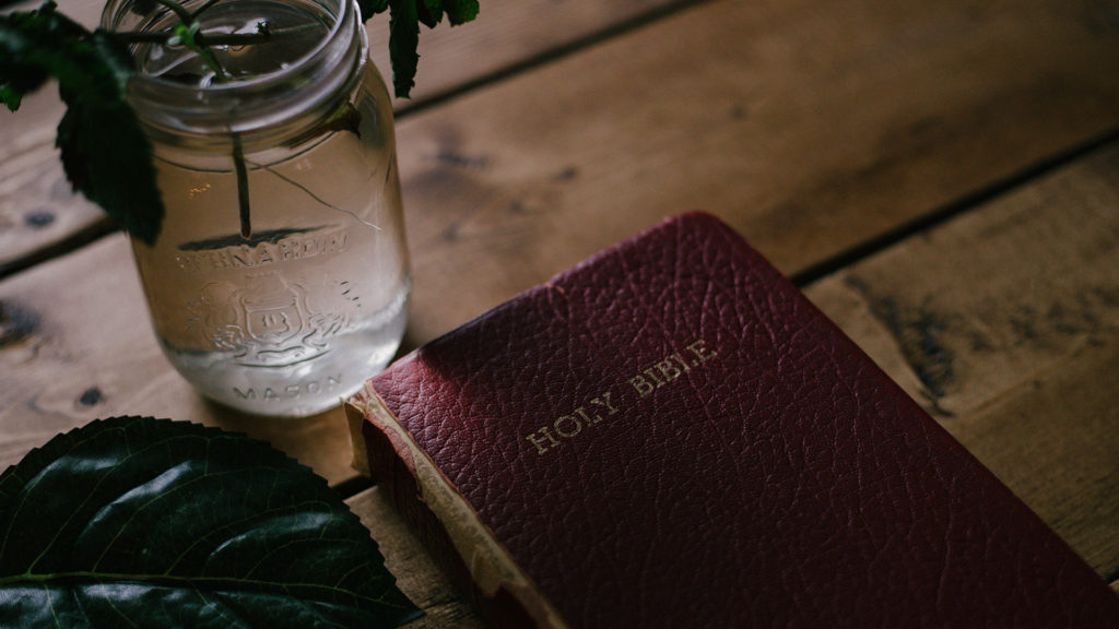 Holy-Bible-beside-clear-mason-jar-on-table