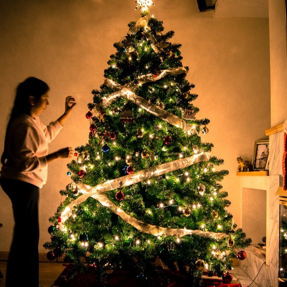 child-standing-in-front-of-Christmas-tree-with-string-lights