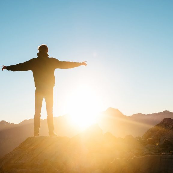 person-standing-on-hill-at-sunrise