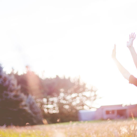 woman-hands-up-in-front-of-green-meadows